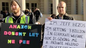 Två män demonstrerar mot Amazon och Jeff Bezos.