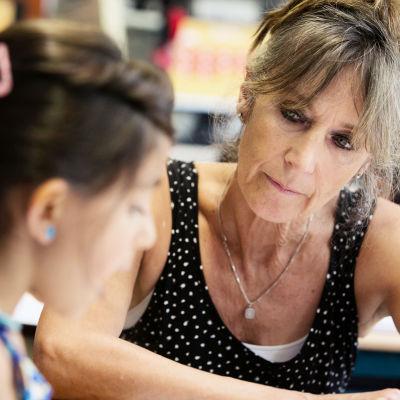 Läraren Kiet hjälper en av sina elever vid en pulpet.