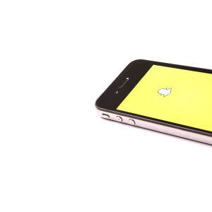 Älypuhelin jonka näytöllä Snapchat-logo.