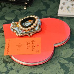 På ett bord ligger en anteckningsbok format som ett rött hjärta. Ovanpå den finns en liten portmonnä och ett armband samt en lapp där det står God jul! 10 år.