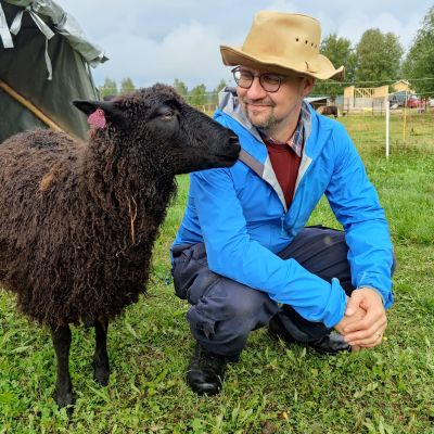 Mies katsoo mustaa, hymyilevää lammasta