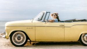 Nainen istuu autossa.