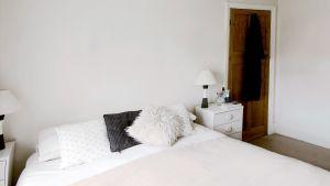 En dubbelsäng som är snyggt bäddad, ljusa färger, vit vägg, nattduksbord med lampa på båda sidorna.