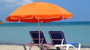 Aurinkotuoli ja -varjo rannalla.