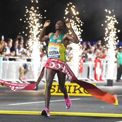 Lelisa Desisa springer över mållinjen och i målbandet.
