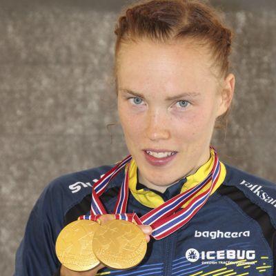 Tove Alexandersson visar upp medaljer.