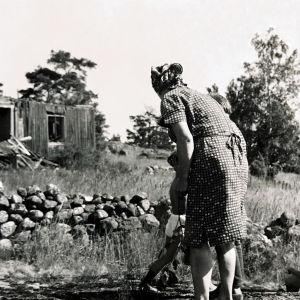 Saaristossa otetussa kuvassa huivipäinen nainen takaapäin kuvattuna nuori poika hänen edessä, taustalla rapistunut autiotalo.