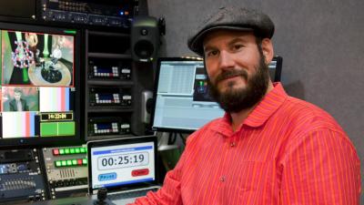TV-producenten och regissören Mikael Tunér sitter framför TV-skärmar i en TV-studio.