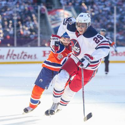 Patrik Laine skrinnar med en Oilers-spelare i hasorna.