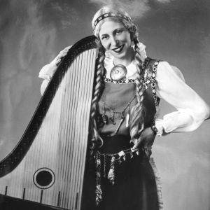 Kansallispukuinen ja palmikkopäinen Ulla Katajavuori kanteleen kanssa.