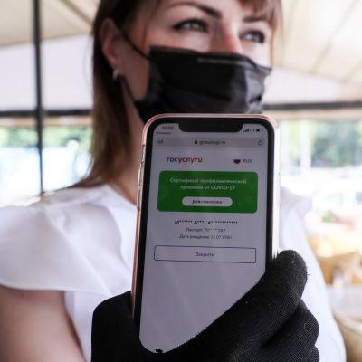 Maskiin pukeutunut tarjoilija näyttää puhelinta, jossa koronatodistus.
