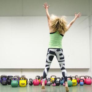 Nainen hyppää jumppasalissa ilmaan kädet ja jalat x-asennossa