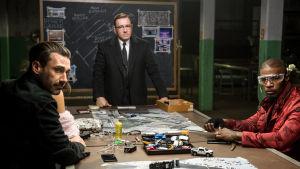 Buddy (Jon Hamm), Doc (Kevin Spacey) och Bats (Jamie Foxx) sitter vid ett bord och planerar ett rån.