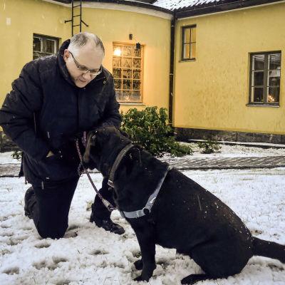 Man på knä med hund.