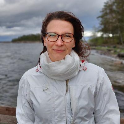 Kvinna med glasögon och mörkt hår står vid en strand och ser mot kameran