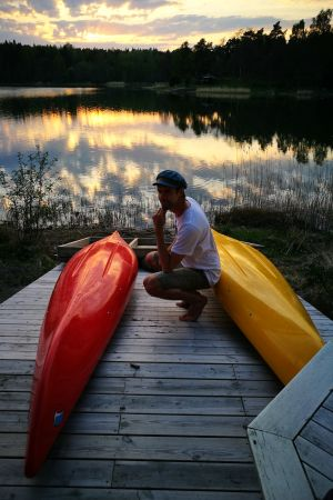 Oliver Kivi sitter på en brygga med två kanoter.
