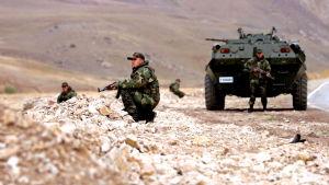 Soldater i kamouflagedräkt står på knä runt ett pansarfordon.