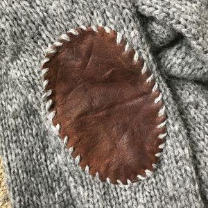 En läderlapp fastsydd på armbågen av en stickad tröja