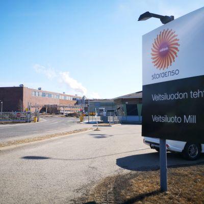 Kyltti, jossa teksti Stora Enso Veitsiluodon tehtaat. Taustalla näkyy punatiilisiä tehdasrakennuksia ja tehtaan portti.