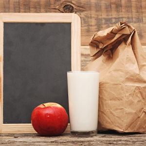 Ett äpple och ett glas mjölk samt en brun papperskass.