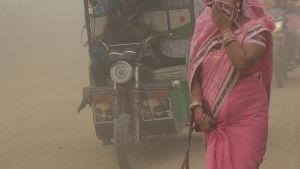 Kvinna försöker skydda sig mot luftföroreningar i New Delhi i Indien.