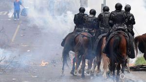 Tårgas, demonstranter och ridande poliser i huvudstaden Quito den 8 oktober 2019.