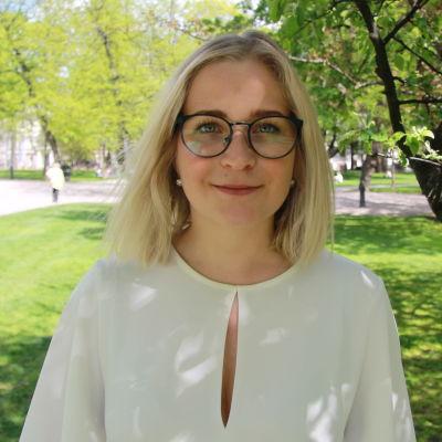 Anita Westerholm står i en park och tittar in i kameran.