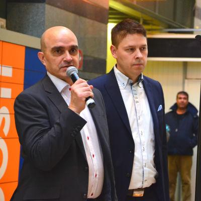 Två män och en kvinna i medelåldern står i ett köpcentrum. Männen har mörk kavaj och vit skjort, kvinnan mörk kavaja och blå tröja. Mannen längst till vänster håller en mikrofon i handen.