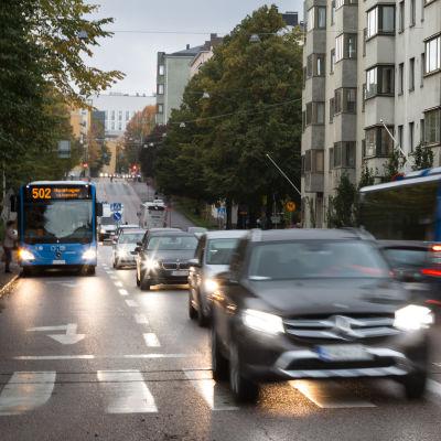 Bilar åker på en väg inne i Helsingfors centrum.