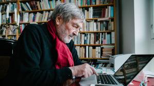 Claes Andersson tietokoneen ääressä.