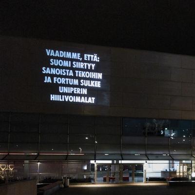 projicerad text på Kiasma: Vaadimme että Suomi siirtyy sanoista tekoihin ja Fortum sulkee Uniperin hiilivoimalan