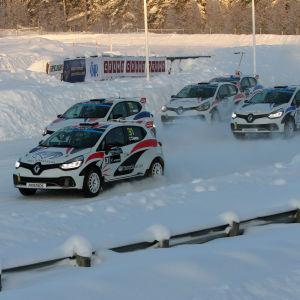 rallycrossbilar kör i hög fart på isbana.