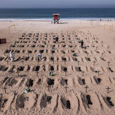 Brasiliassa aktivistien uimarannalla kaivamat haudat kuvastavat koronaviruksen uhreja.