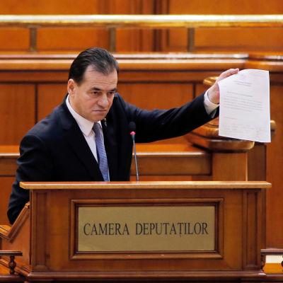 Ludovic Orban puhujanpöntössä paperinippu kädessään.