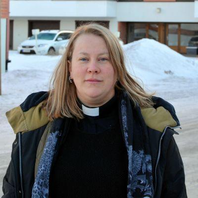 Prästen Eva Töhlix utomhus i vintermiljö.