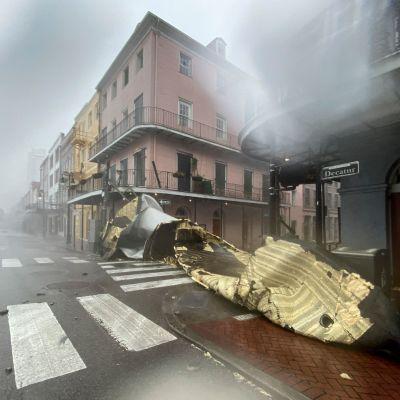 Lösrivna tak ligger på en tom gata. På bilden syns det att regnar och blåser hårt.