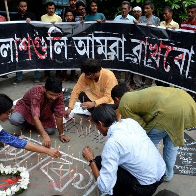 Människor tänder ljus för att hedra offren i attacken mot en restaurang i Dhaka, Bangladesh, den 2 juli 2016.