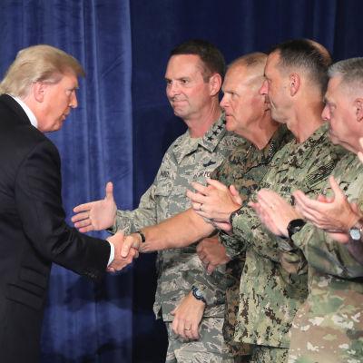 Donald Trump skakar hand med militära ledare innan han håller tal om USA:s närvaro i Afghanistan.