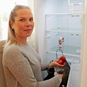 Ida Larsson visar upp innehållet i matsvinnskylskåpet i Arabiastranden.