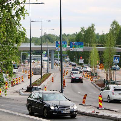 Trafik och nyplanterade björkar på Mattgårdsvägen i Esbo.