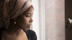 Kirjailija Nura Farah katsoo ikkunasta ulos