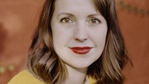Bild på Eva Frantz i gul tröja mot röd bakgrund.