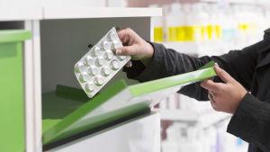 En person tar ut läkemedel ur ett skåp på ett apotek.