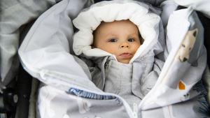 En baby i en vagn iklädd kläder från mammalådan 2019.