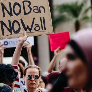 Demonstration mot inreseförbudet. En kvinna håller en skylt och en annan kvinna klädd i hijab syns i förgrunden.