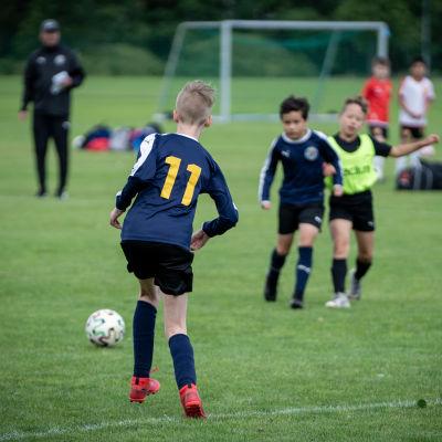 Tre pojkar spelar fotboll på Helsinki cup.