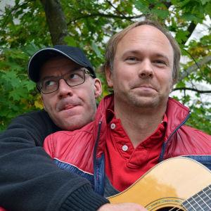 Marcus Granberg håller i gitarren medan Tomas Nyberg skojsamt spelar på den.