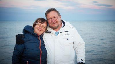 Raili ja Juha M. Venäläinen poseeraavat hymyillen ulkoiluvaatteissa rannalla taustallaan avoin ulappa.