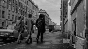 kolme henkilöä kävelee Leningradissa pois päin kadulla