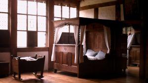 Parsäng och vagga i trä i ett sovrum.